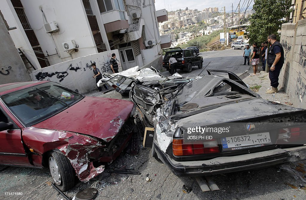 Residents remove crushed cars as they return to their homes near near the Bilal bin Rabah mosque in the Abra district of the southern city of Sidon on June 25, 2013, after troops seized control of the headquarters of a radical Sunni sheikh whose supporters battled the army for two days, killing 16 soldiers.