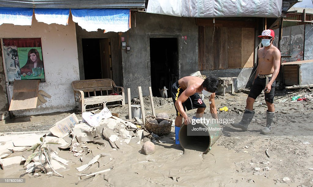 Residents remove mud and flood waters from their house brought about by typhoon Bopha in the southern Philippine township of New Bataan, Philippines. More than 500 people have been killed and scores of others remain missing after Typhoon Bopha, the strongest storm to hit the Philippines this year, pounded the region.