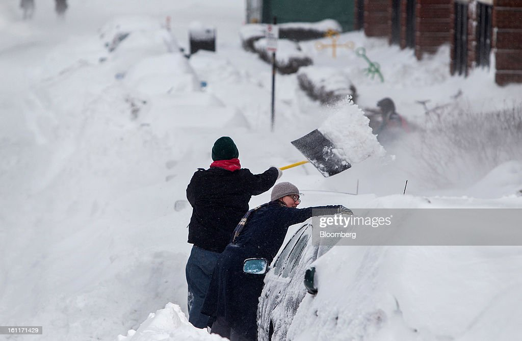 Residents remove snow from their car after Winter Storm Nemo in Boston, Massachusetts, U.S., on Saturday, Feb. 9, 2013. More than two feet of snow fell on parts of the U.S. Northeast as high winds left hundreds of thousands of people in the region without power, closed highways and forced the cancellation of 4,700 flights. Photographer: Scott Eisen/Bloomberg via Getty Images