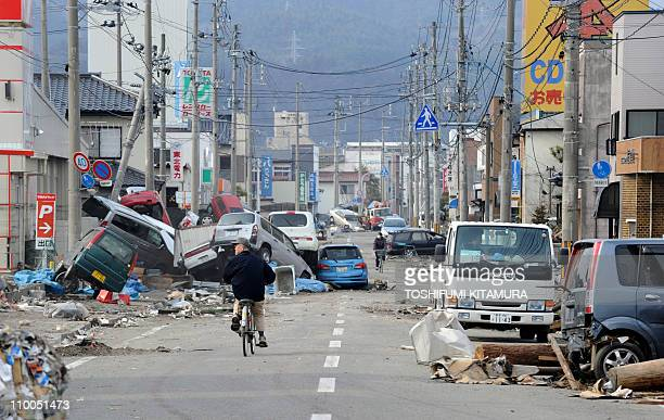 Residents ride bicycles down a road littered with debris and crushed vehicles in the town of Ofunato in Iwate prefecture on March 14 2011 three days...