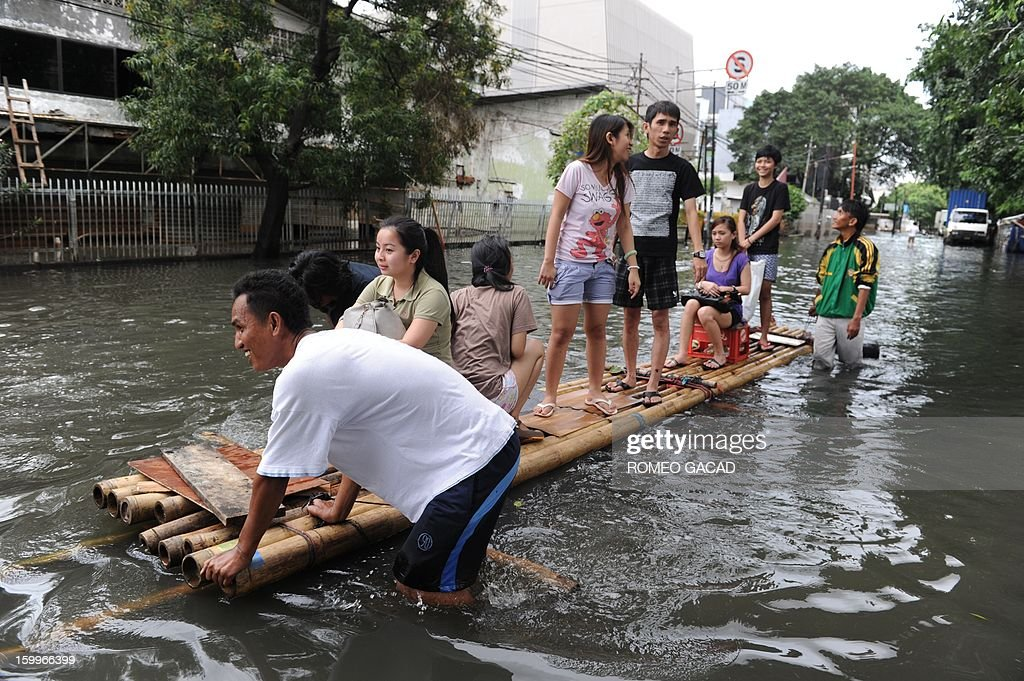 Residents ride improvised rafts to travel in a flooded neighborhood in Jakarta on January 24, 2013. Indonesia's National Disaster Mitigation Agency (BNPB) said more than 30,000 people were displaced while 20 people died during the widespread flooding that hit Jakarta as the weather bureau forecast more rains in the coming days. AFP PHOTO / ROMEO GACAD