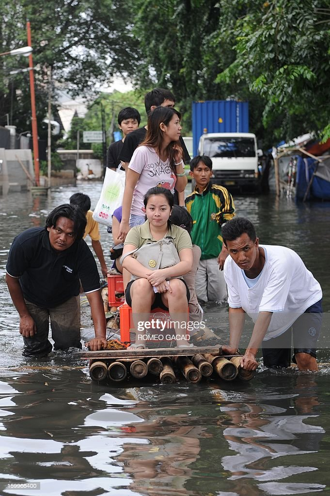 Residents ride improvised rafts to travel in a flooded neighborhood in Jakarta on January 24, 2013. Indonesia's National Disaster Mitigation Agency (BNPB) said more than 30,000 people were displaced while 20 people died during the widespread flooding that hit Jakarta as the weather bureau forecast more rains in the coming days.