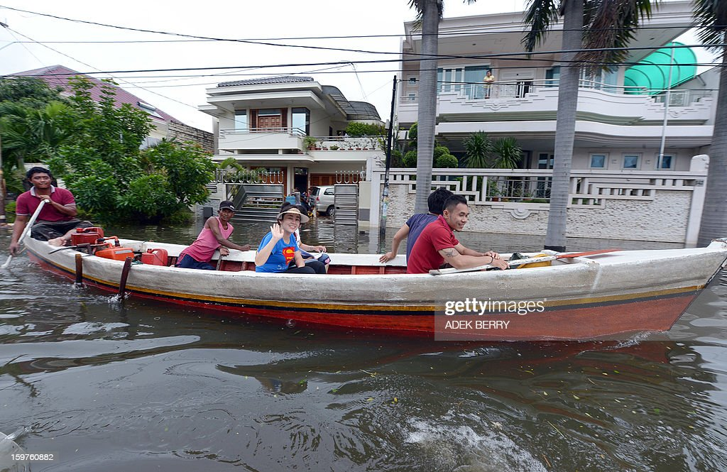 Residents ride in a rented boat down a flooded street at a luxury housing complex in Jakarta on January 20, 2013. The death toll from floods in Indonesia's capital Jakarta rose to 15 on January 19 after rescuers found another four bodies. The floods are the worst to hit the capital since 2007 and forced 18,000 people from their homes.