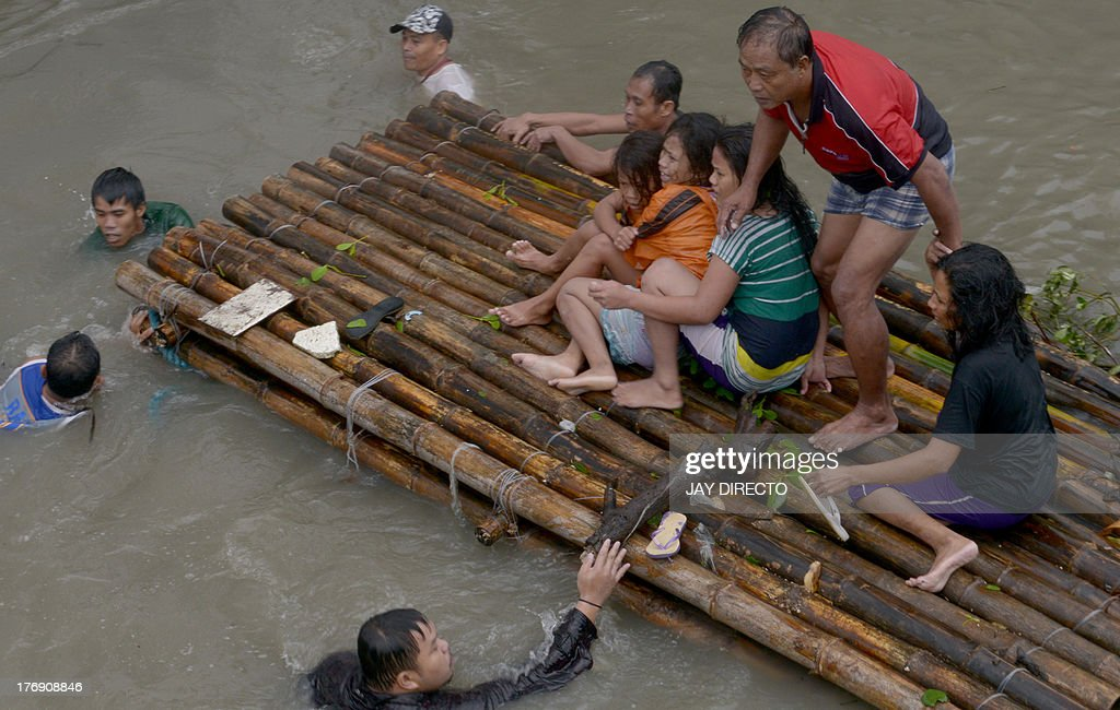 Residents ride on a bamboo raft over floodwaters in the farming town of Novaleta, some 26 kilometres outside Manila on August 19, 2013. Torrential rain paralysed large parts of the Philippine capital on August 19 as neck-deep water swept through homes, while floods in northern farming areas claimed at least one life. AFP PHOTO / Jay DIRECTO