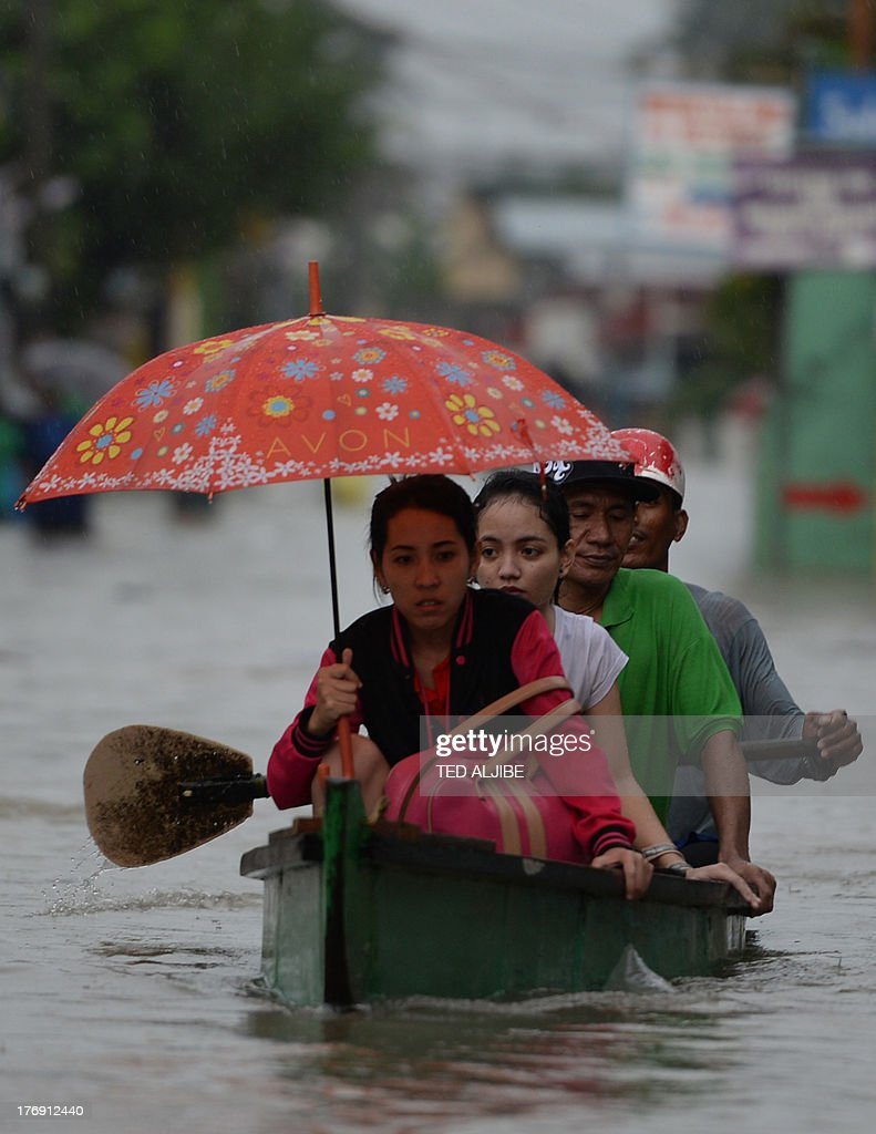 Residents ride on a wooden boat as they head back home on a flooded street in Cavite, southwest of Manila on August 19, 2013. Torrential rain paralysed large parts of the Philippine capital August 19, as neck-deep water swept through homes, while floods in northern farming areas claimed at least one life.