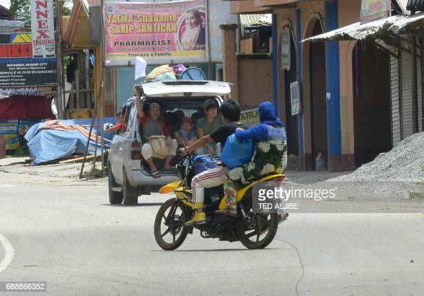Residents riding in their vehicle with a white flag evacuate from their homes in Marawi in southern island of Mindanao on May 27 2017 The Philippine...