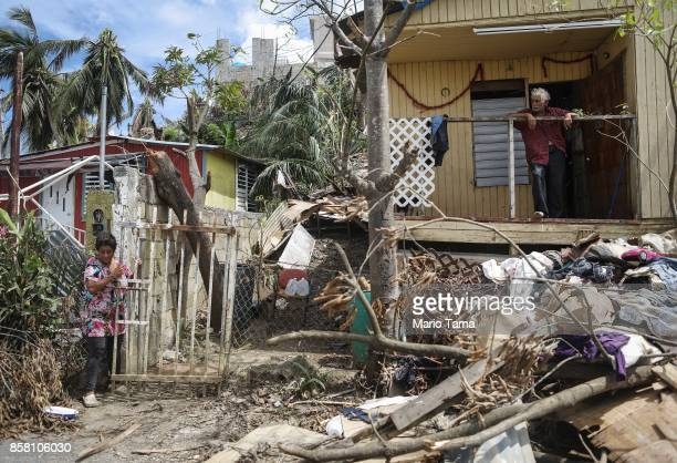 Residents Rosa and Errol gather at their damaged home without power or running water about two weeks after Hurricane Maria swept through the island...