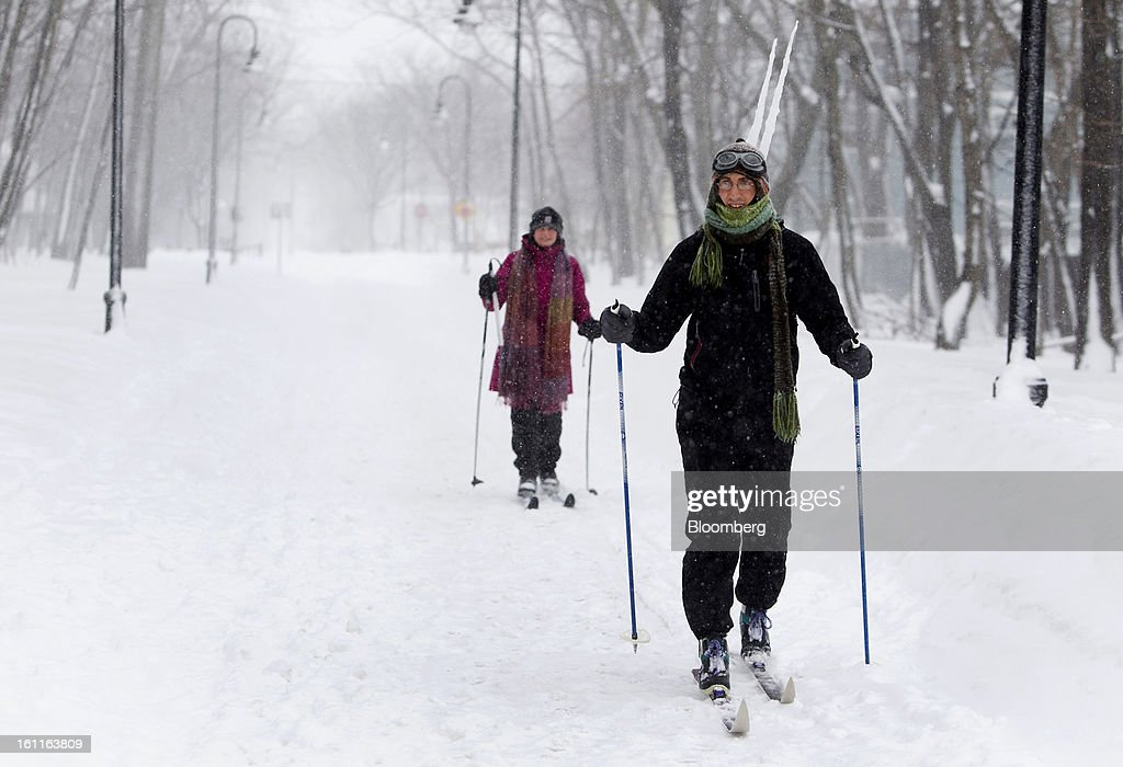 Residents Ross Hoffman, right, and Elsa Waldman ski down the Grove-Cedar bike path after Winter Storm Nemo in Somerville, Massachusetts, U.S., on Saturday, Feb. 9, 2013. More than two feet of snow fell on parts of the U.S. Northeast as high winds left hundreds of thousands of people in the region without power, closed highways and forced the cancellation of 4,700 flights. Photographer: Kelvin Ma/Bloomberg via Getty Images