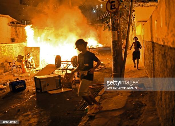 Residents run for cover during violent clashes between protestors and Brazilian Police Special Forces in a favela near Copacabana in Rio de Janeiro...