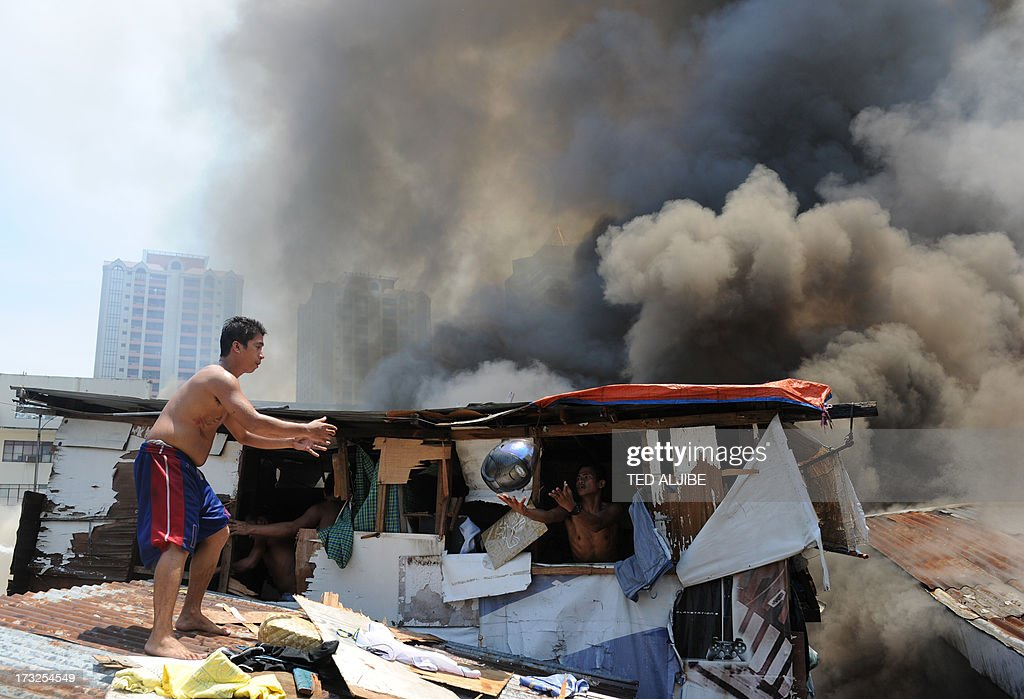 Residents salvage belongings from their burning house as a fire engulfs shanty town at the financial district of Manila on July 11, 2013, leaving more than 1,000 people homeless according to city officials. There were no immediate reports of casualties from the blaze, which occurred mid-morning amid government plans to relocate thousands of families living in areas vulnerable to floods and typhoons.