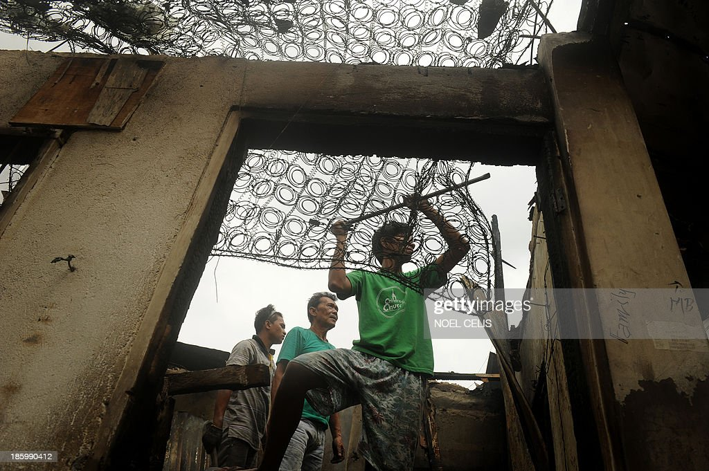 Residents search for salvageable materials among debris after an overnight fire razed a slum area in Manila in October 27, 2013. More than 500 houses were burned leaving 2000 familes homeless and two children dead according to local media reports.