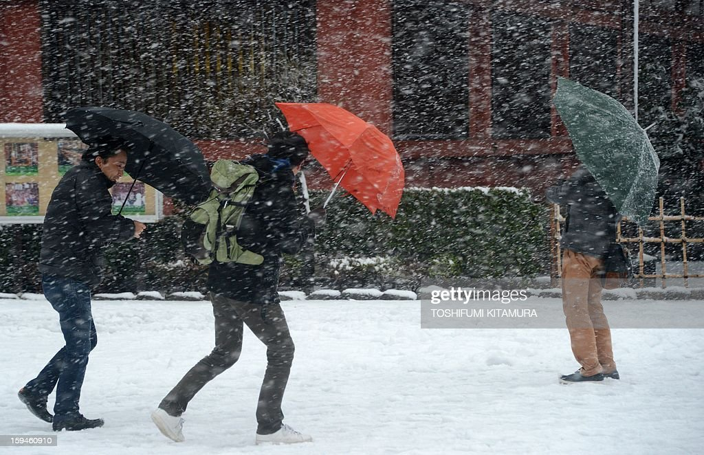 Residents shelter under their umbrellas as it snows at Sensoji temple in the Asakusa area in Tokyo on January 14, 2013. A storm system grasped central Japan on January 14, causing heavy snow fall around the Japanese capital. AFP PHOTO / TOSHIFUMI KITAMURA
