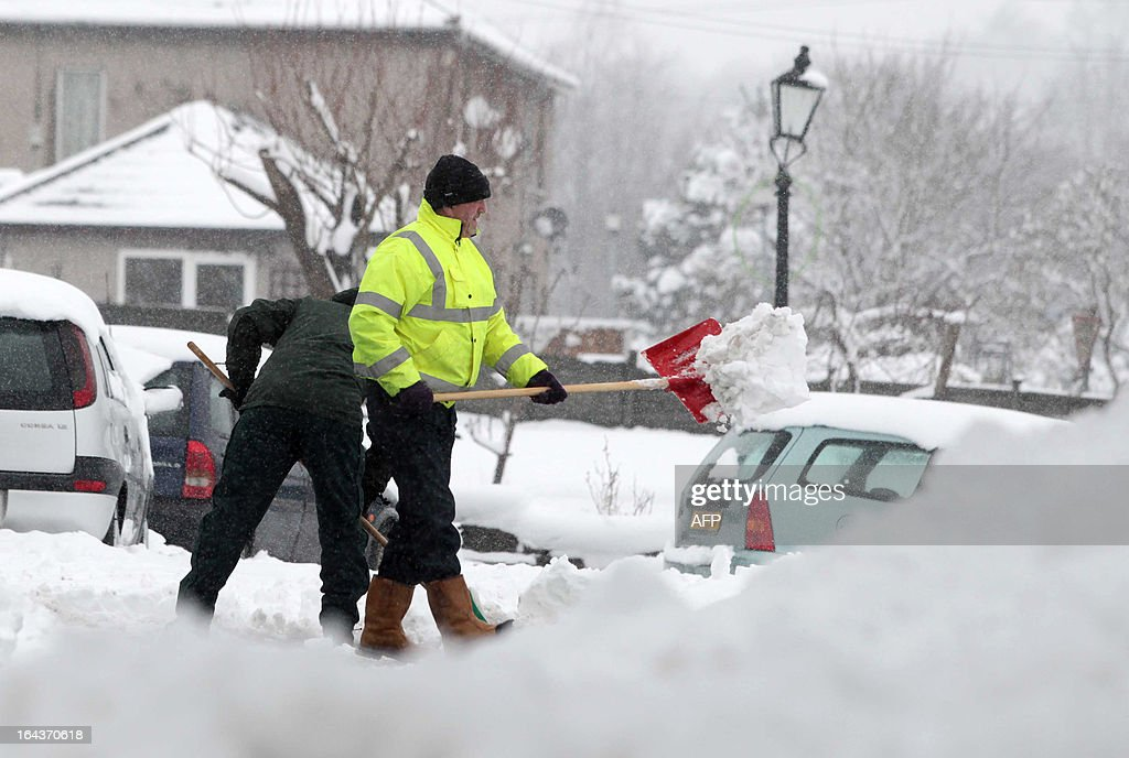 Residents shovel snow from pavements near Bakewell in Derbyshire on March 23, 2013. Heavy unseasonal snowfall hit parts of central and northern England, Scotland and Ireland, bringing sub-zero temperatures and travel disruption across the country. AFP PHOTO / LINDSEY PARNABY