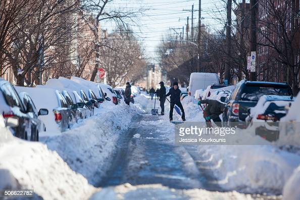 Residents shovel their cars and street out on January 24 2016 in Philadelphia Pennsylvania Millions of people are digging themselves out after a...