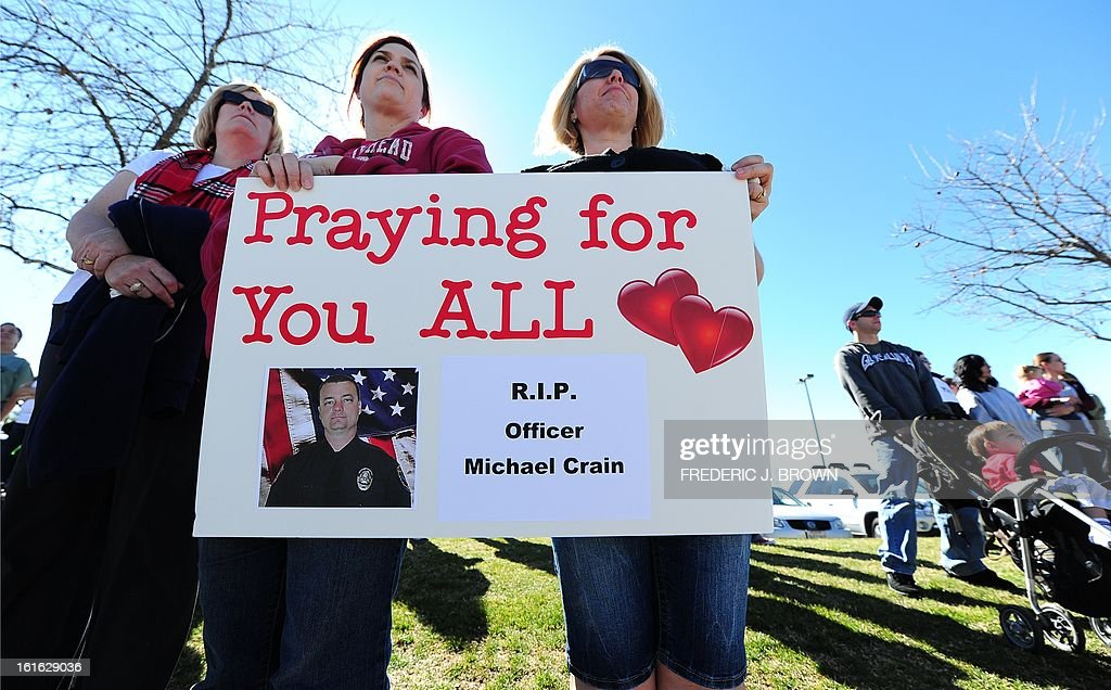 Residents show their support as they await the departure of the convoy and hearse carrying the body of slain Riverside police officer Michael Crain following a memorial service at the Grove Community Church in Riverside, California, on February 13, 2013. Law enforcement personnel from across the state, including local dignitaries, military veterans, colleagues, friends and loved ones of Crain gathered to pay their final respects to the policeman killed last week in what the city's police chief described as a 'cowardly ambush.'' Crain was fatally shot February 7 when he and his partner ran afoul of fugitive Christopher Jordan Dorner. AFP PHOTO / Frederic J. BROWN