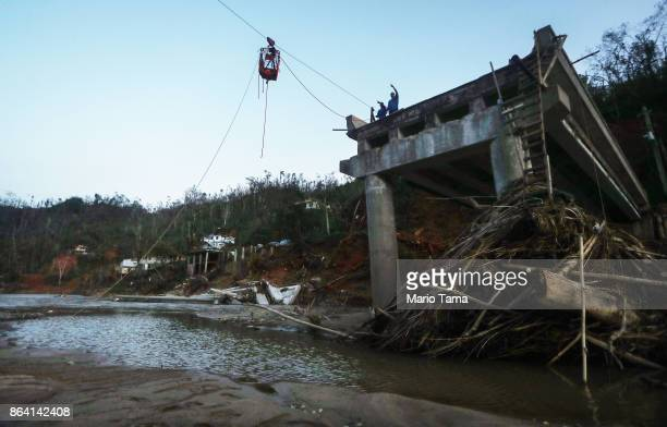 Residents signal while manuevering a shopping cart filled with supplies across a rope and pulley system spanning a broken bridge over the Vivi River...
