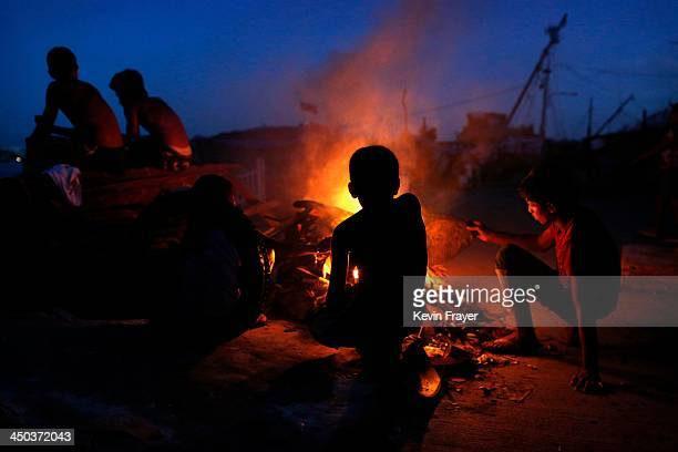 Residents sit around a fire used for light and cooking in an area destroyed in the aftermath of Typhoon Haiyan on November 18 2013 in Tacloban...