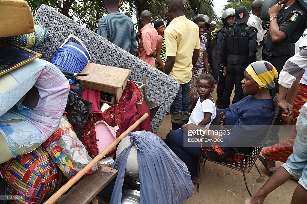 Residents sit next to their belongings after leaving their homes as a destruction operation is taking place on September 2, 2014 in Attecoube, a poor sector of Abidjan, in order to remove unstable habitations built on hill slopes deemed as landslide prone. About 39 people died on June 2014 in Abidjan because of landslides since the beginning of the rainy season. 350,000 people live in Attecoube, most of them in terrible conditions and on unstable ground, making them particularly vulnerable to floods and landslides.