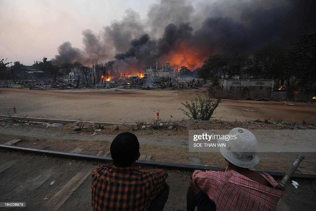 Residents sit on a railway track watching buildings burn around a mosque in riot-hit Meiktila, central Myanmar on March 21, 2013. At least 10 people have been killed in riots in central Myanmar, an MP said on March 21, prompting international concern at the country's worst communal unrest since a wave of Buddhist-Muslim clashes last year. AFP PHOTO/ Soe Than WIN