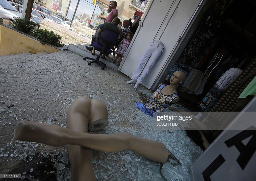 Residents sit outside their damaged shops near the Bilal bin Rabah mosque in the Abra district of the southern city of Sidon on June 25, 2013, after troops seized control of the headquarters of a radical Sunni sheikh whose supporters battled the army for two days, killing 16 soldiers.