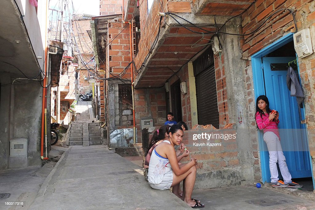 Residents sit outside their homes in a small alley way next to the urban spaces constructed near Spain Library (Biblioteca Espana) built for the cultural and social transformation of the city built on the hill in the midst of slums on January 5, 2013 in Medellin, Colombia. The notorious slums of Medellin have gone through urban and educational projects to improve the quality of life for its residence.