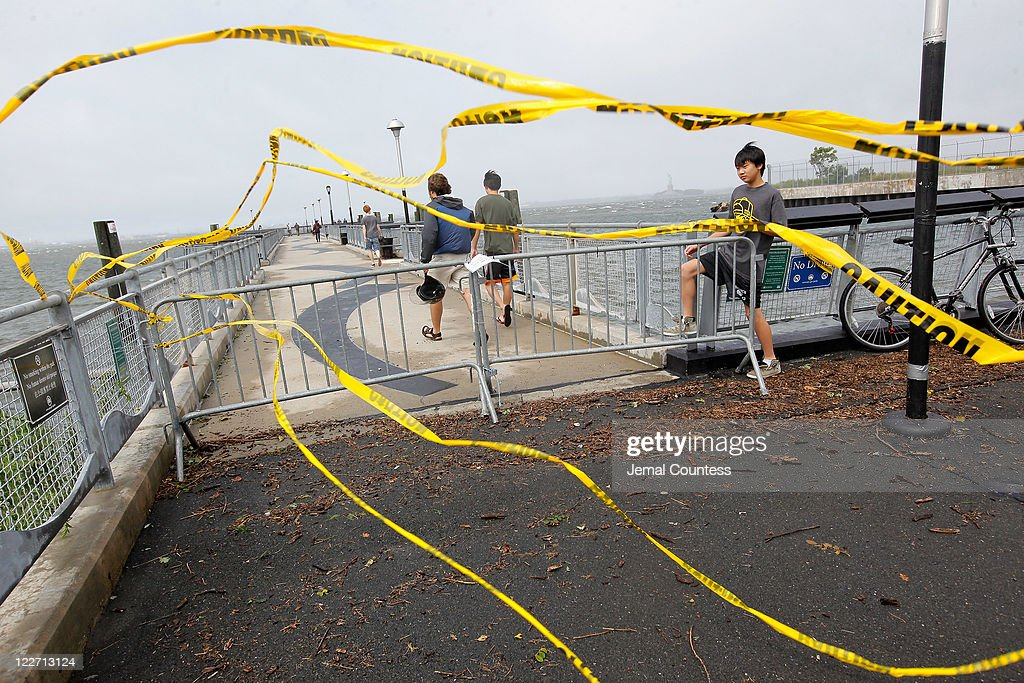 Residents slip past a barricade to enter Valentino Pier in Red Hook Brooklyn as the skies clear in the aftermath of Hurricane Irene on August 28, 2011 in New York City. The hurricane hit New York as a Category 1 storm before being downgraded to a tropical storm.