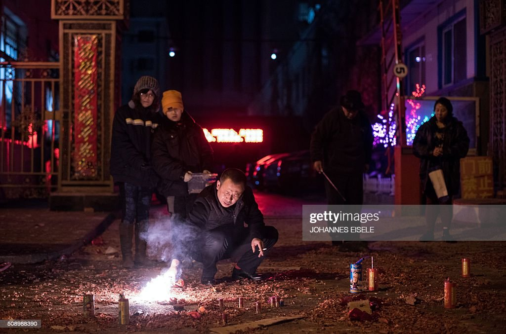 Residents stand along a street surrounded by paper left from fireworks set off for Lunar New Year celebrations at the Chinese border town of Dandong, opposite to the North Korean town of Sinuiju, early on February 8, 2016, a day after North Korea said it had successfully put a satellite into orbit. The UN Security Council strongly condemned North Korea's rocket launch on February 7 and agreed to move quickly to impose new sanctions that will punish Pyongyang for 'these dangerous and serious violations.' With backing from China, Pyongyang's ally, the council again called for 'significant measures' during an emergency meeting held after North Korea said it had put a satellite into orbit with a rocket launch. AFP PHOTO / JOHANNES EISELE / AFP / JOHANNES EISELE