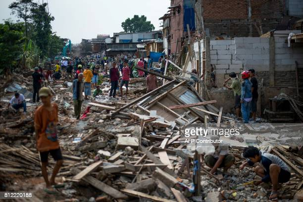 TOPSHOT Residents stand amid the debris of their homes which were torn down in the evicted area of the Bukit Duri neighbourhood located on the...