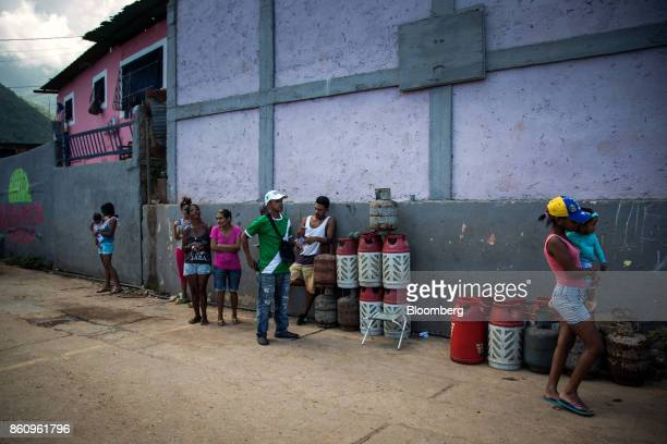 Residents stand beside empty Petroleos de Venezuela SA gas canisters as they wait for their weekly delivery in La Guaira Venezuela on Friday Oct 6...