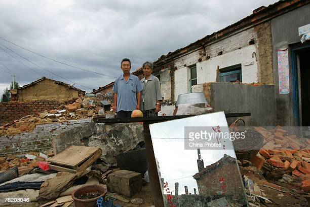 A Residents stand in front of their home being demolished in a coal mining subsidence area August 21 2007 in Jiaohe of Jilin Province China Jiaohe...