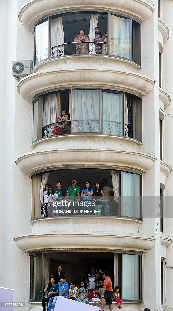 Residents stand in the balcony of an upmarket apartment in the posh locality of Bandra in Mumbai as they watch India's first soapbox race in Mumbai on December 2, 2012. Mumbai experiences similar urbanisation challenges as other fast growing cities in developing countries: wide disparities in housing between the affluent, middle-income and low-income segments of the population. Despite the recent economic growth, there is still vast poverty, unemployment and therefore poor housing conditions for a huge section of the population. AFP PHOTO/INDRANIL MUKHERJEE
