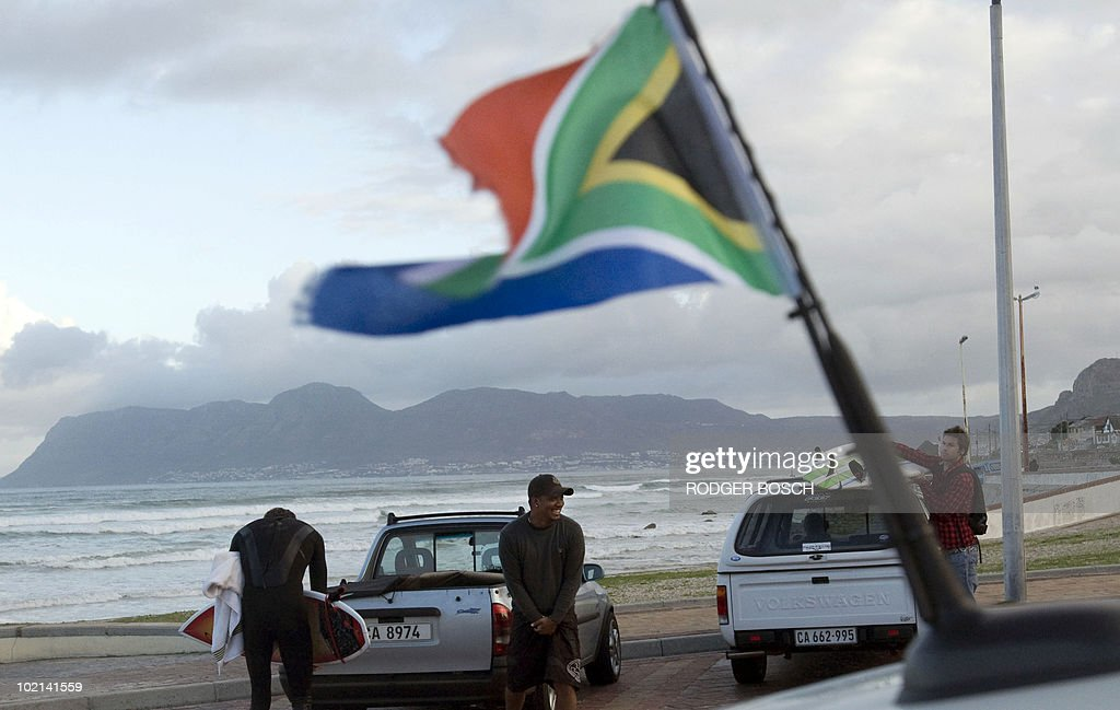 Residents stand near a car parked at Muizenburg Beach, a popular surfing spot in Cape Town, on 16 June, 2010 moments before South Africa take on Uruguay in their World Cup Group A football match.