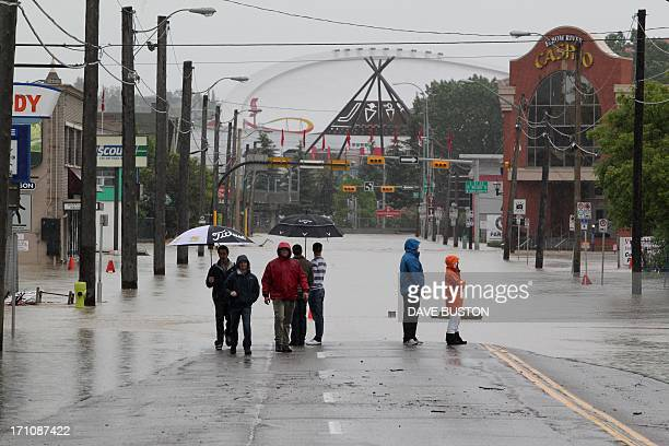 Residents stand near rising waters before the Olympic Saddledome in Calgary Alberta Canada June 21 2013 Flooding forced the evacuation on Friday of...
