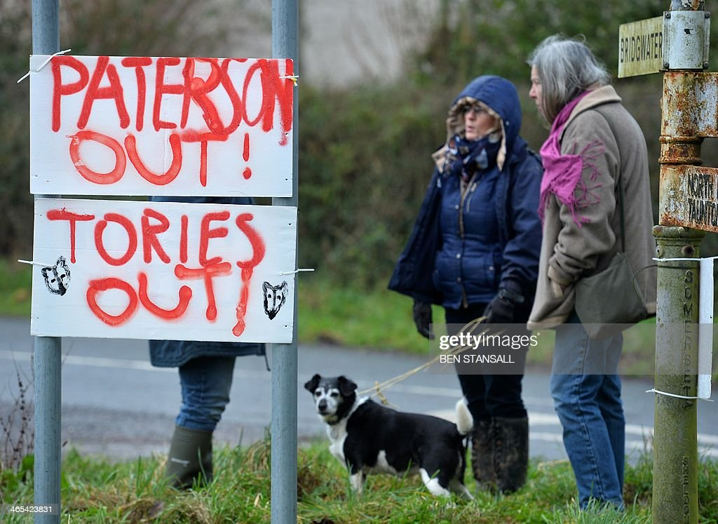 Residents stand next to placards reading 'Paterson out' and 'Tories out' referring to Environment Secretary Owen Paterson who visited the area and...
