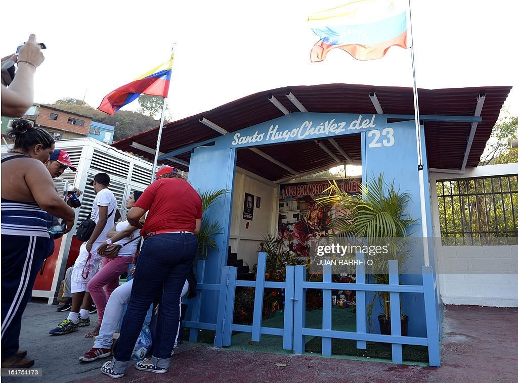 Residents stand next to the newly inaugurated Santo Hugo Chavez del 23 chapel, at the 23 de Enero neighbourhood, in the surroundings of the museum where the remains of President Chavez lay, in Caracas on March 27, 2013. AFP PHOTO