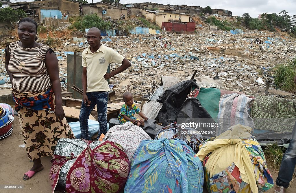 Residents stand next to their belongings after leaving their homes as a destruction operation is taking place on September 2, 2014 in Attecoube, a poor sector of Abidjan, in order to remove unstable habitations built on hill slopes deemed as landslide prone. About 39 people died on June 2014 in Abidjan because of landslides since the beginning of the rainy season. 350,000 people live in Attecoube, most of them in terrible conditions and on unstable ground, making them particularly vulnerable to floods and landslides.