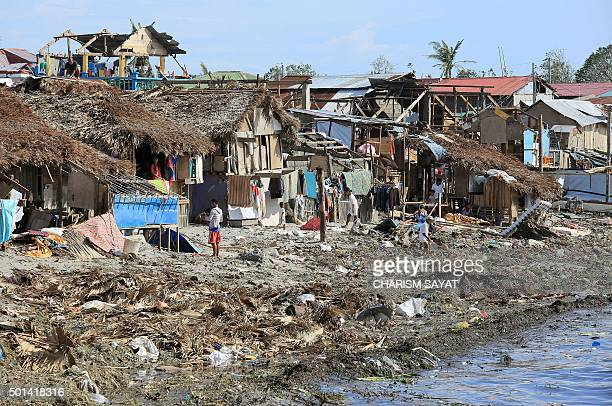 Residents stand next to their damaged houses with blown out roofs after typhoon Melor hit Bulan town Sorsogon province south of Manila on December 15...