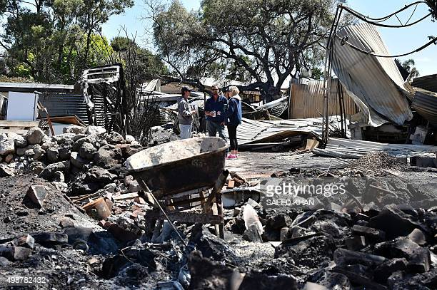 Residents stand next to their fire damaged property following a bushfire in Freeling north of Adelaide on November 26 2015 Hundreds of firefighters...