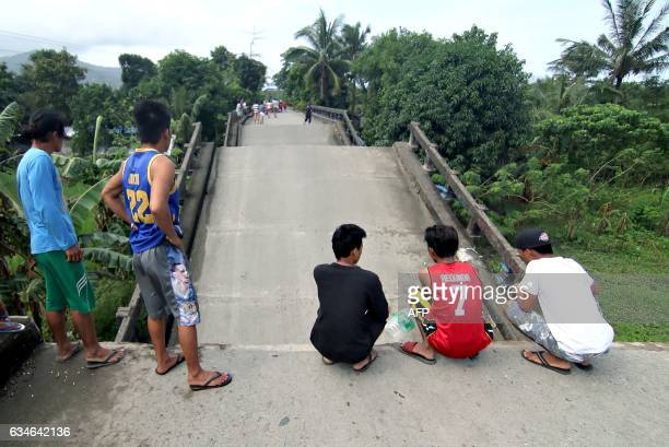 Residents stand on one end of a bridge linking the city of Surigao to nearby towns which was damaged after a 65magnitude earthquake struck overnight...