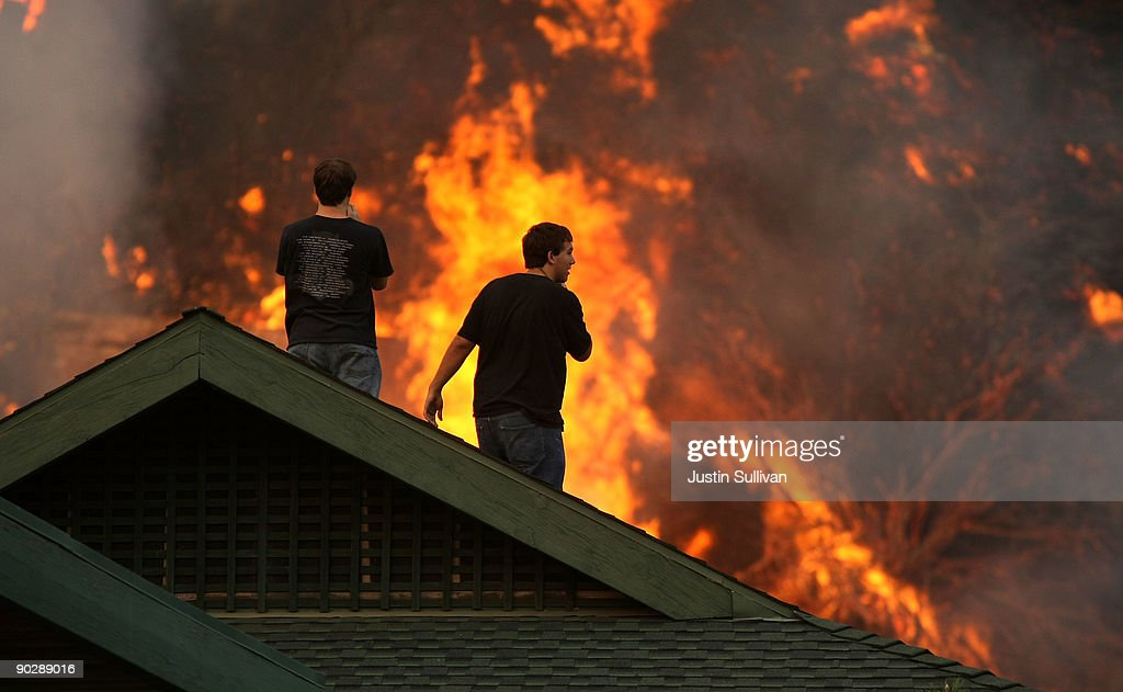 Residents stand on their roof to watch a wildfire burn near their home September 1 2009 in Glendale California Several wildfires have scorched more...