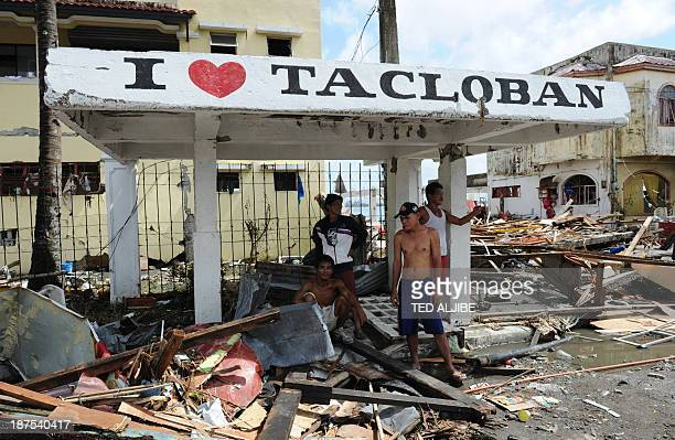 Residents stand under a shelter surrounded by pile of debris washed inland along a road in Tacloban Leyte province central Philippines on November 10...