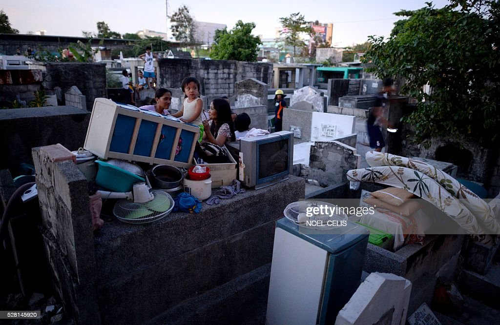 Residents stay on tombs after their makeshift houses were hit by fire that swept over a shanty community inside a public cemetery in Manila on May 4, 2016. No one was hurt in the fire, according to initial reports. / AFP / NOEL