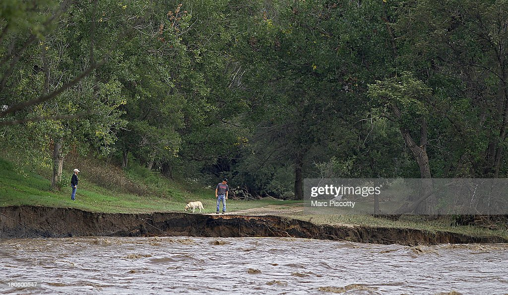 Residents survey erosion along the St. Vrain River on September 13, 2013 in Longmont, Colorado. Heavy rains for the better part of week have fueled widespread flooding in numerous Colorado towns.