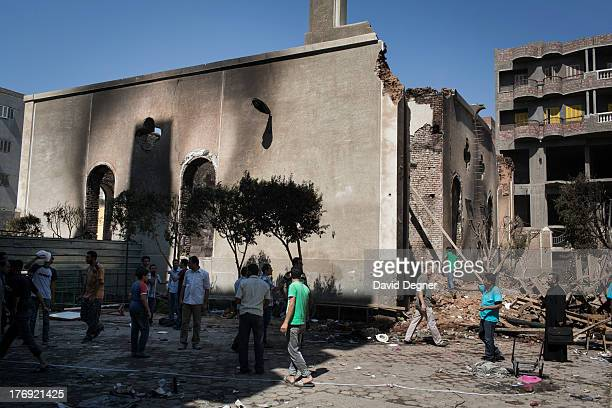 Residents survey the remains of the Evangelical church of Mallawi after it was looted and set on fire Morsi supporters gathered after Friday prayers...