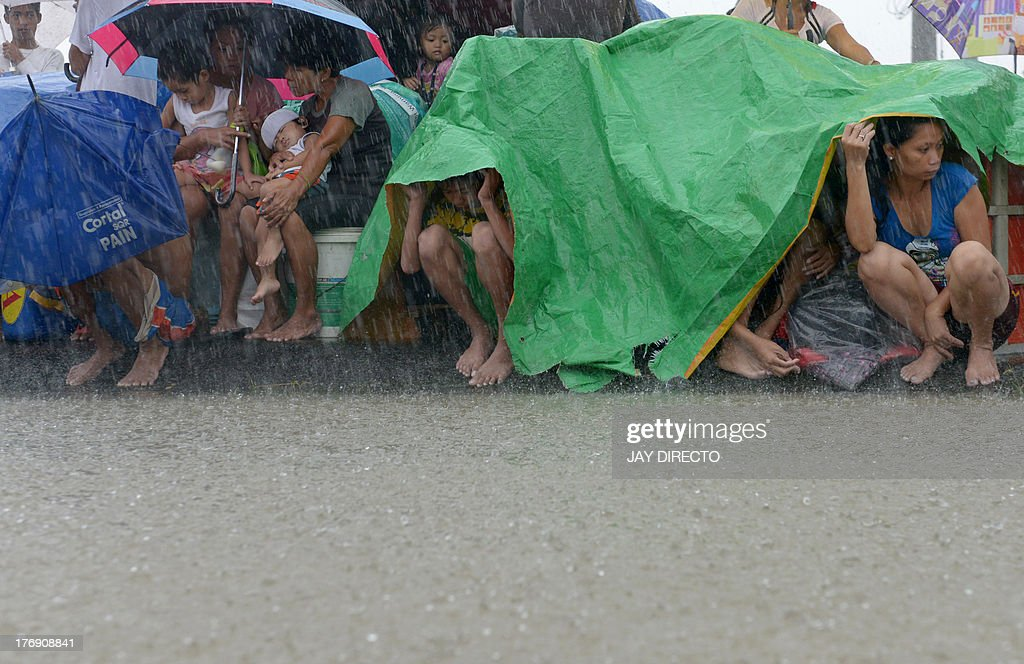 Residents take shelter from the rain after floodwaters inundated their homes in the farming town of Novaleta, some 26 kilometres outside Manila on August 19, 2013. Torrential rain paralysed large parts of the Philippine capital on August 19 as neck-deep water swept through homes, while floods in northern farming areas claimed at least one life. AFP PHOTO / Jay DIRECTO