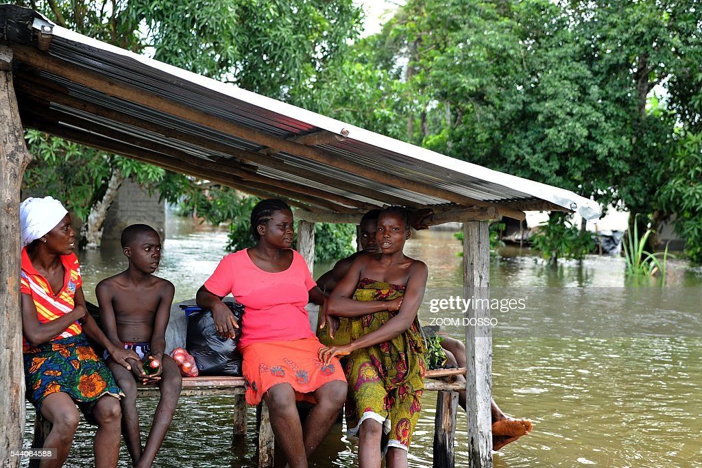 Residents take shelter in a flooded area in Monrovia on July 1, 2016 following heavy rains. Heavy rains have cut the only road access to Liberia's main airport, leaving travellers to cross some sections by canoe, passengers told AFP on July 1. At certain points the sole road between the capital Monrovia and Roberts International Airport is 1.5 metres (five feet) underwater. DOSSO