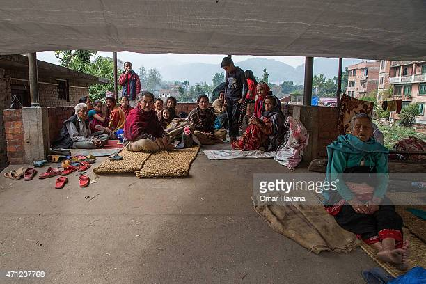 Residents take shelter under a plastic tarp in the city center on April 26 2015 in Bhaktapur Nepal A major 78 earthquake hit Kathmandu midday on...