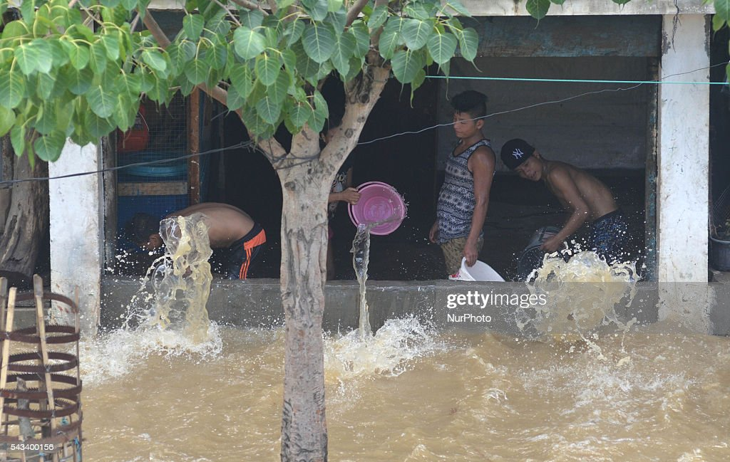 Residents throw flooded water from inside their house with bucket after a heavy monsoon rain in Dimapur, India north eastern state of Nagaland on Tuesday, June 28, 2016. Thousands of people were render homeless after heavy monsoon rain in the state.