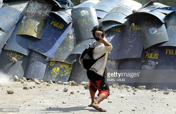 A residents throws a stone and at policemen during a demolition operation in a squatters area in Manila on January 27 2014 The government wants to...