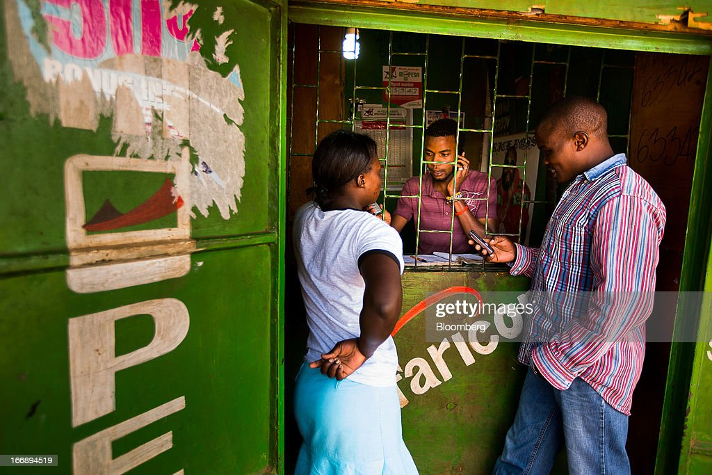 Residents transfer money using the M-Pesa banking service at a store in Nairobi, Kenya, on Sunday, April 14, 2013. In the six years since Kenya's M-Pesa brought banking-by-phone to Africa, the service has grown from a novelty to a bona fide payment network. Photographer: Trevor Snapp/Bloomberg via Getty Images